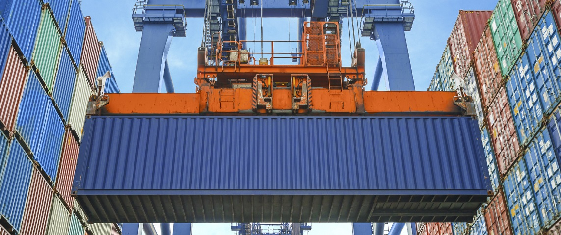 Shore crane loading containers in freight ship
